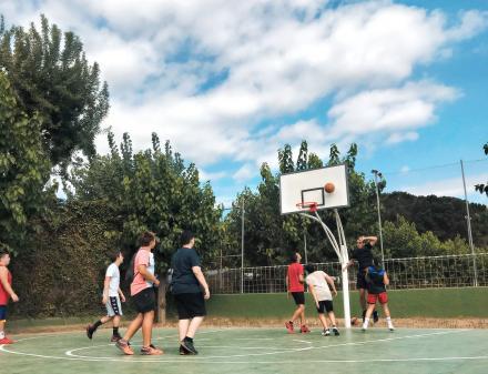 Jongeren op een kampeerbasketbalveld