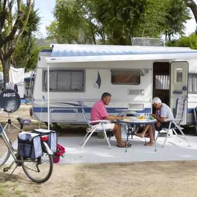 Couple eating in front of a caravan